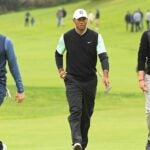 Rory McIlroy, Tiger Woods and Justin Thomas walk down the fairway.