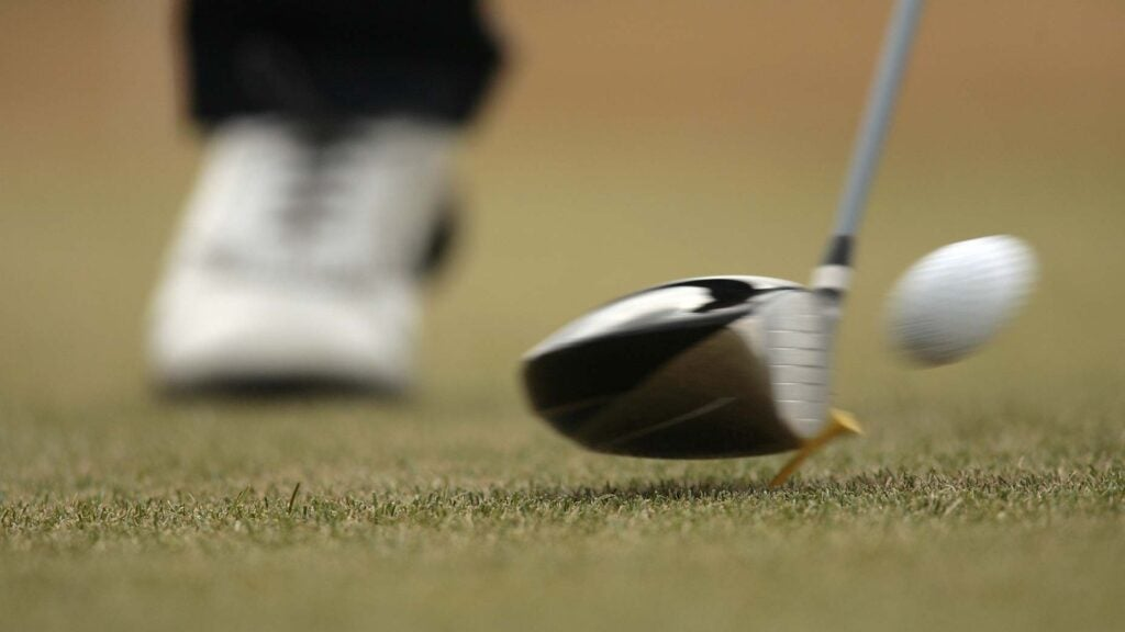 a golfer hits his driver off the tee