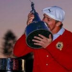 Bryson DeChambeau kisses the trophy.