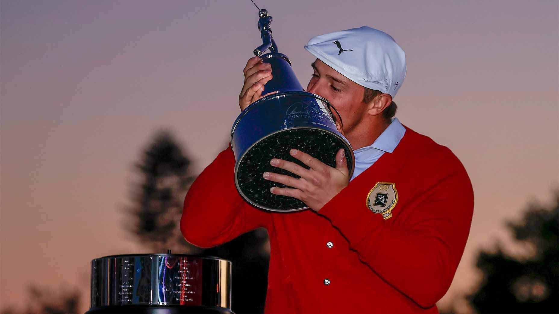 Bryson DeChambeau kisses the trophy.
