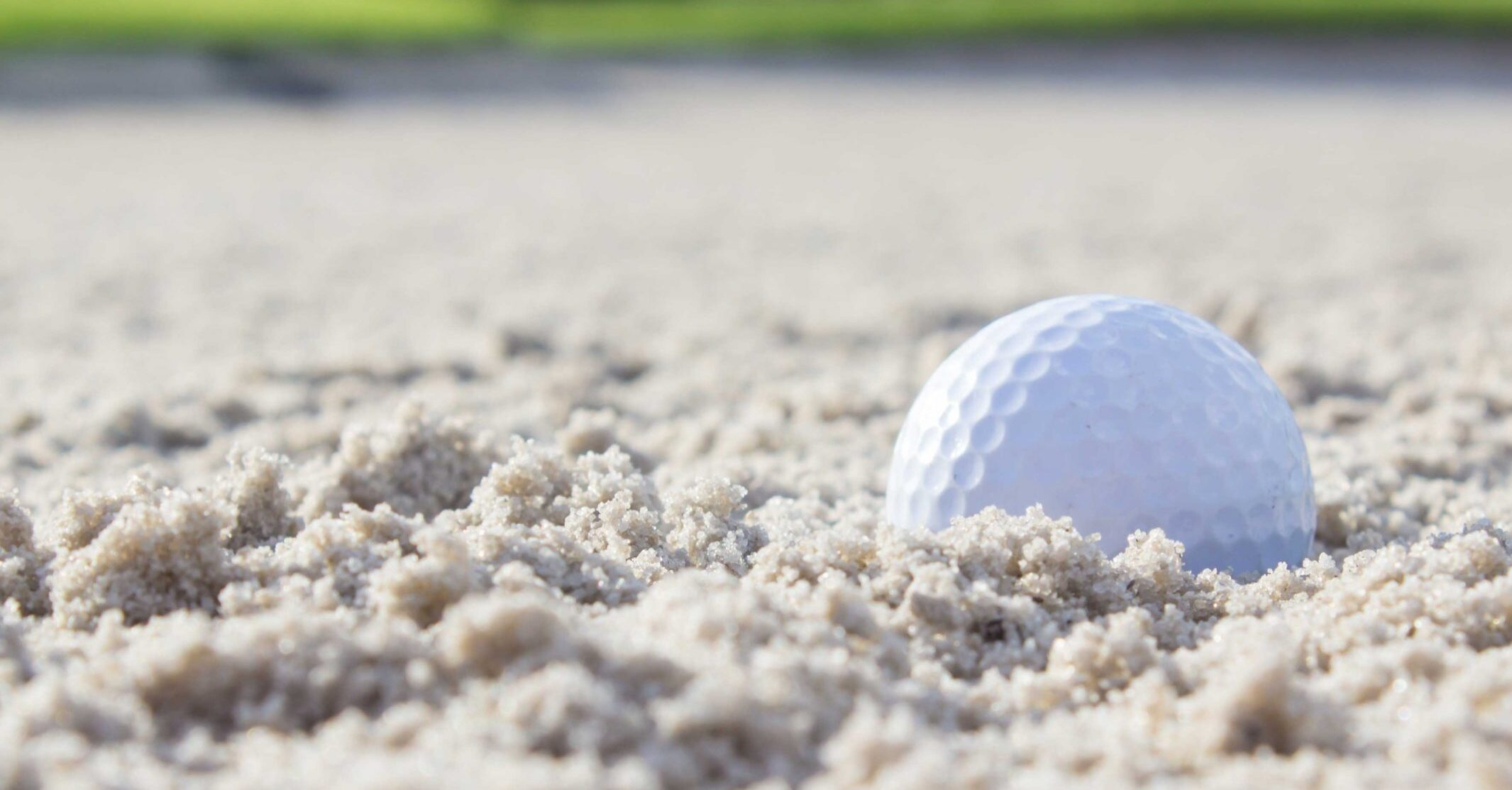 golf ball sits in sand bunker on golf course