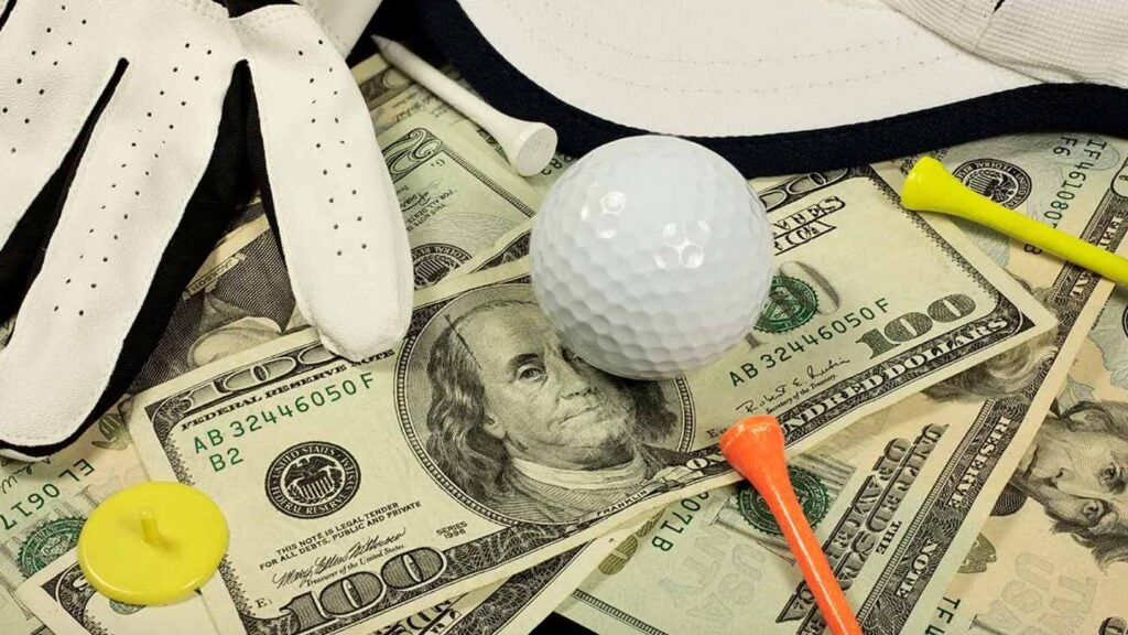 A golf ball, golf glove,and golf tee sit on a pile of U.S. dollars