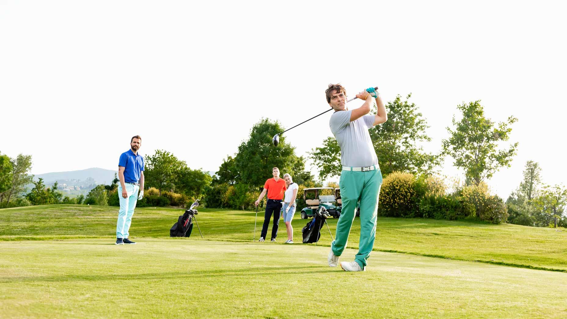 man hits golf ball