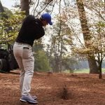 Rory McIlroy hits a ball out of the pinestraw.