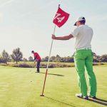 golfer holding flagstick