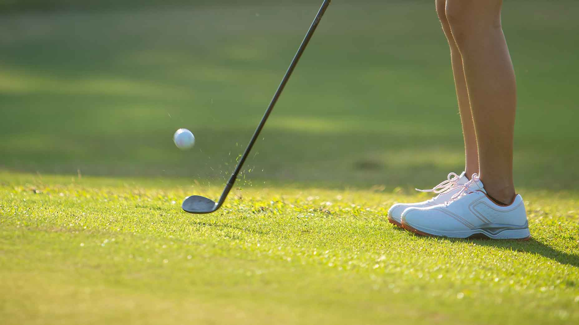 a woman chipping onto a green.