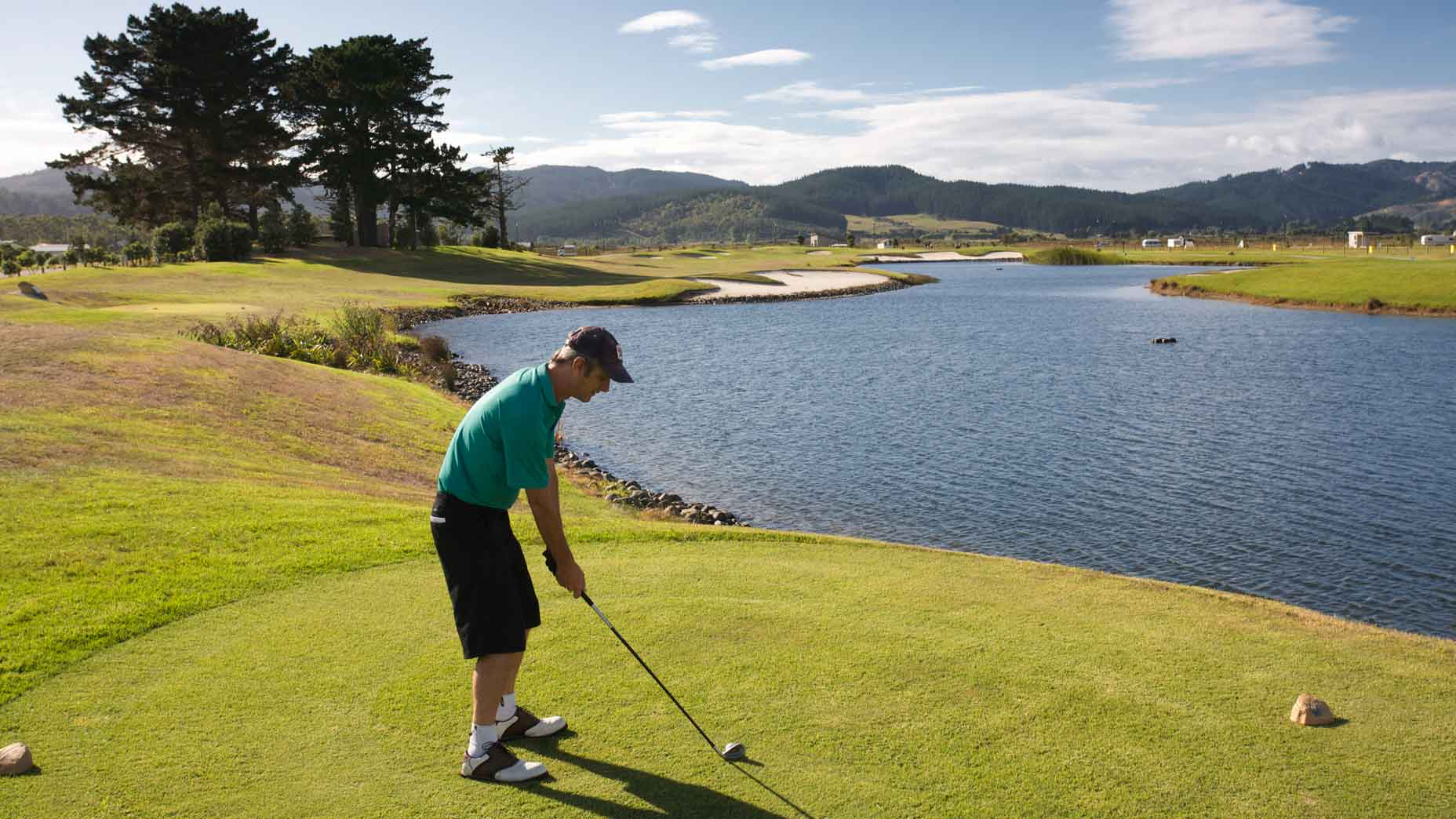 golfer tee shot over water