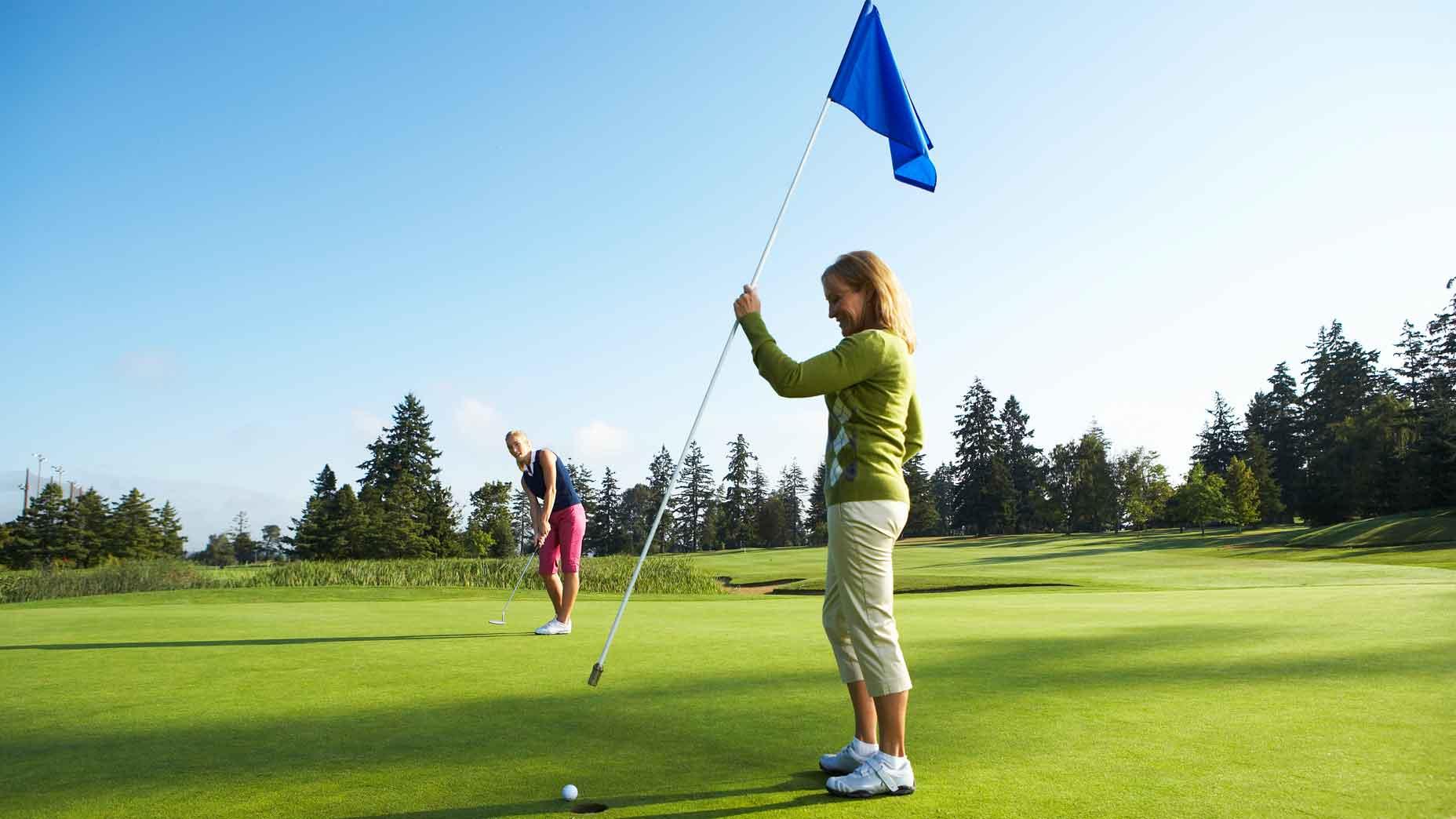 golfers holding flagstick