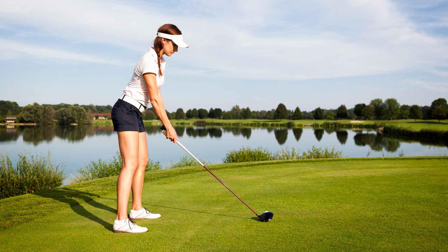 woman golf shot over water
