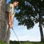 golfer behind tree