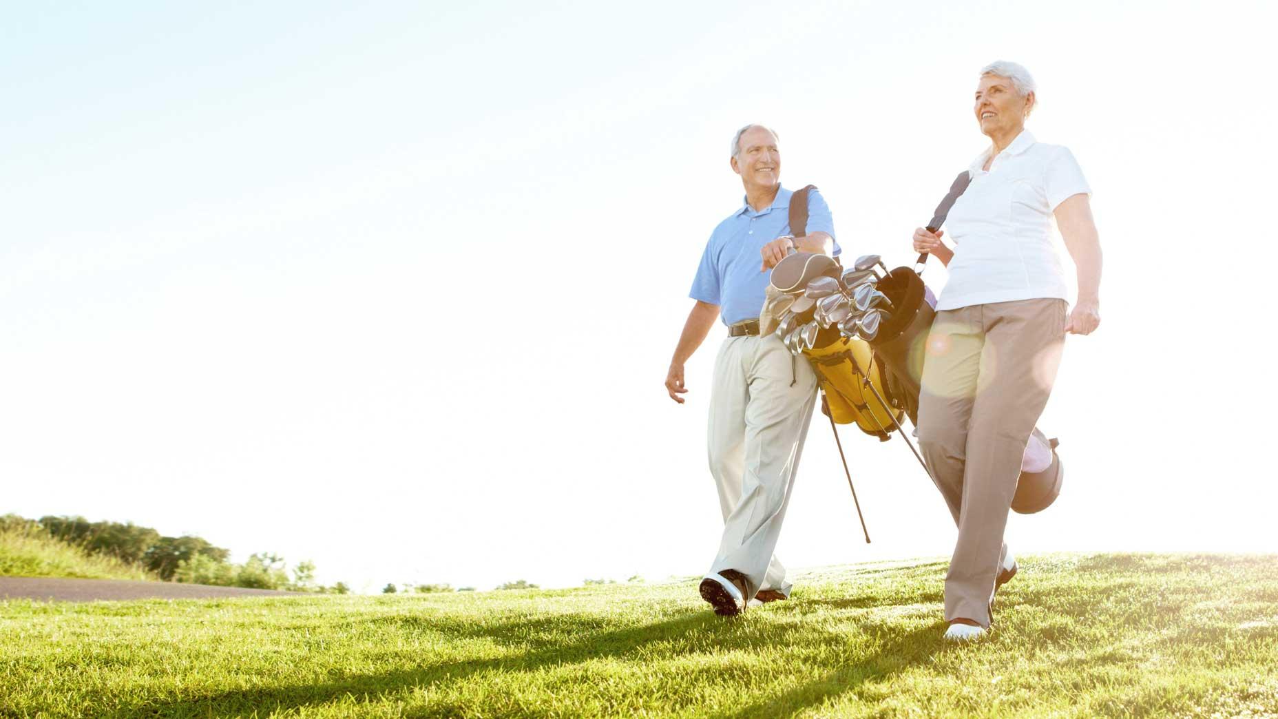 old golfers walk the fairway