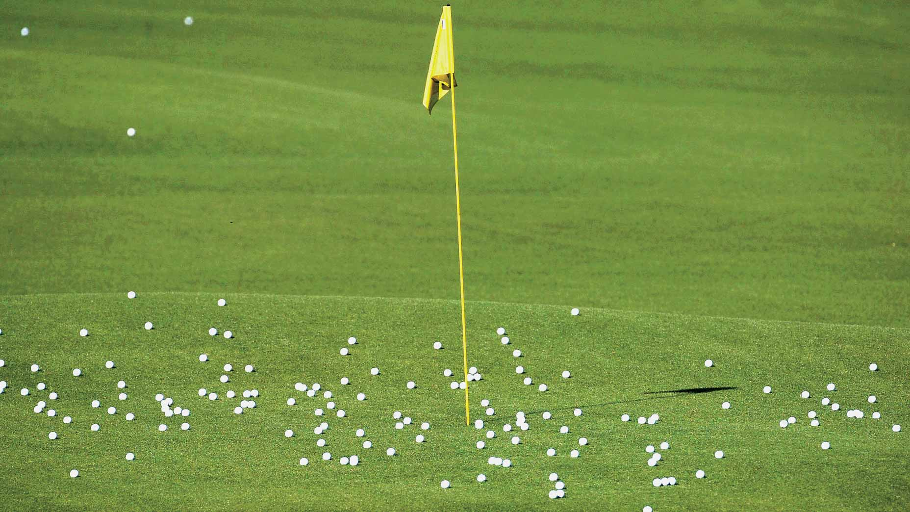 Golf practice balls sit on a practice green around a yellow flagstick