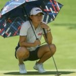 Danielle Kang uses an umbrella to find relief from the heat at Kasumigaseki.