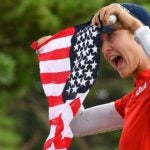 Nelly Korda holds up the american flag at the olympics.