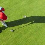 A golfer hits a short putt.