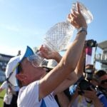 woman drinks from trophy