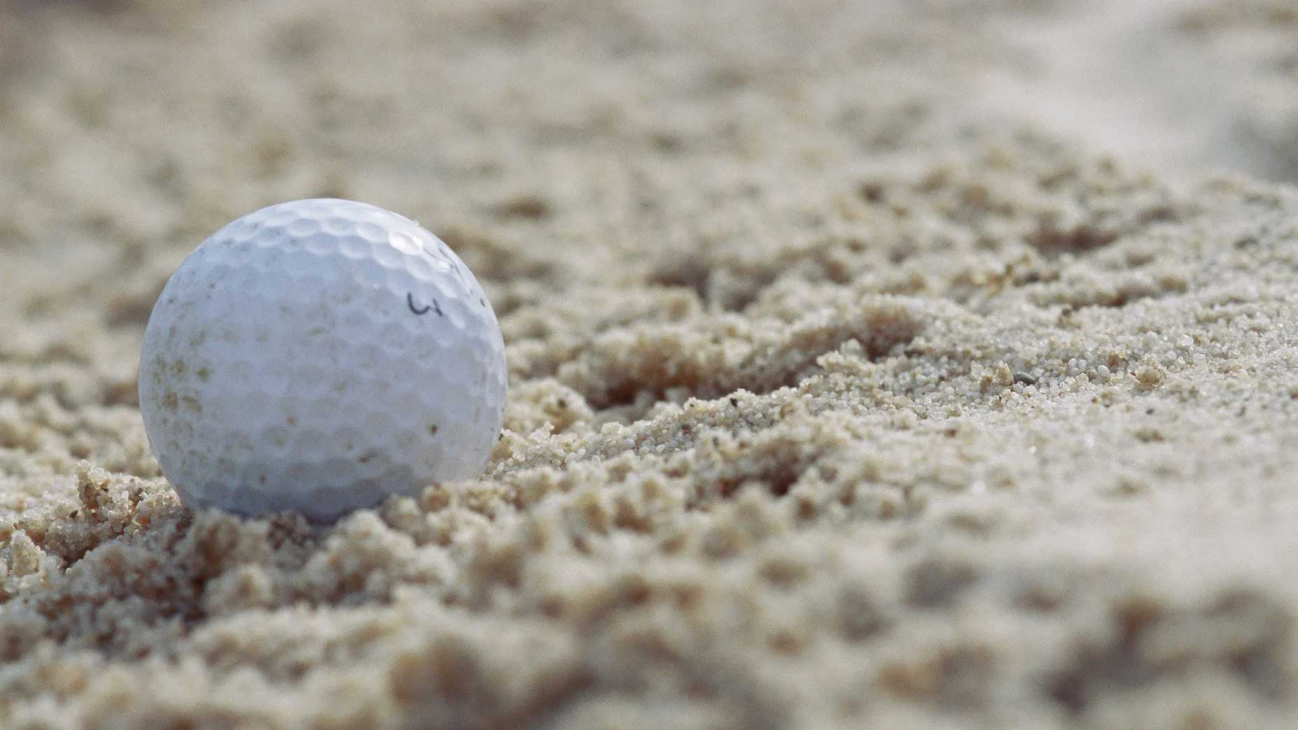 A golf ball rests in the sand on a hole.