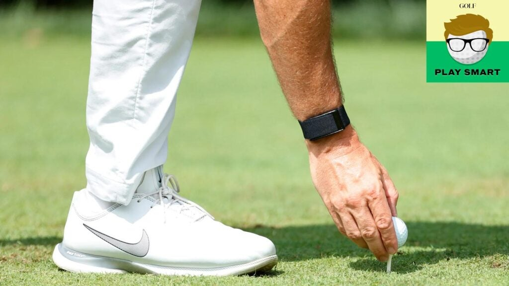 Pro tees up golf ball