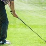 Golfer prepares to hit golf ball