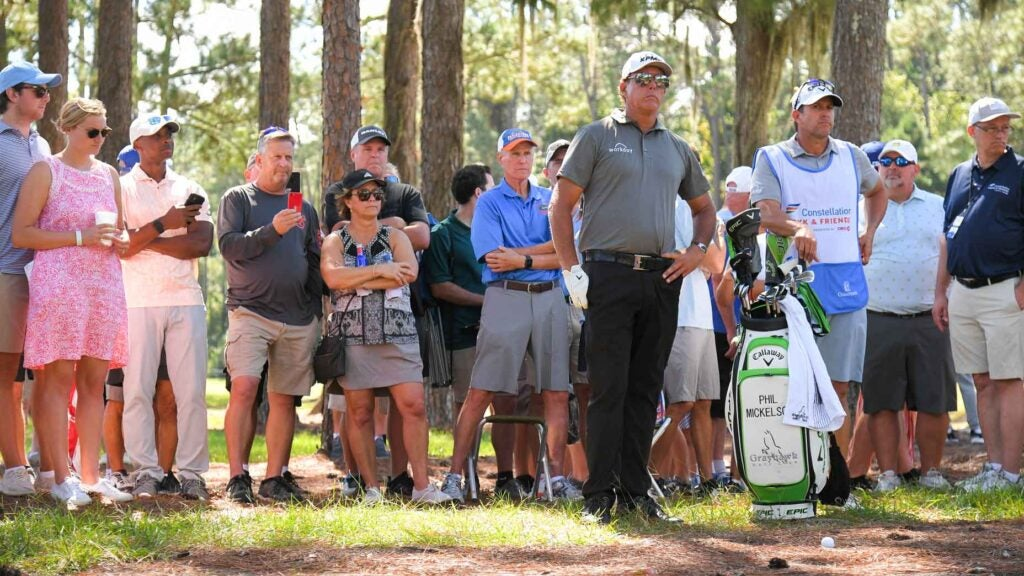 Phil Mickelson stands in pine straw surround by gallery