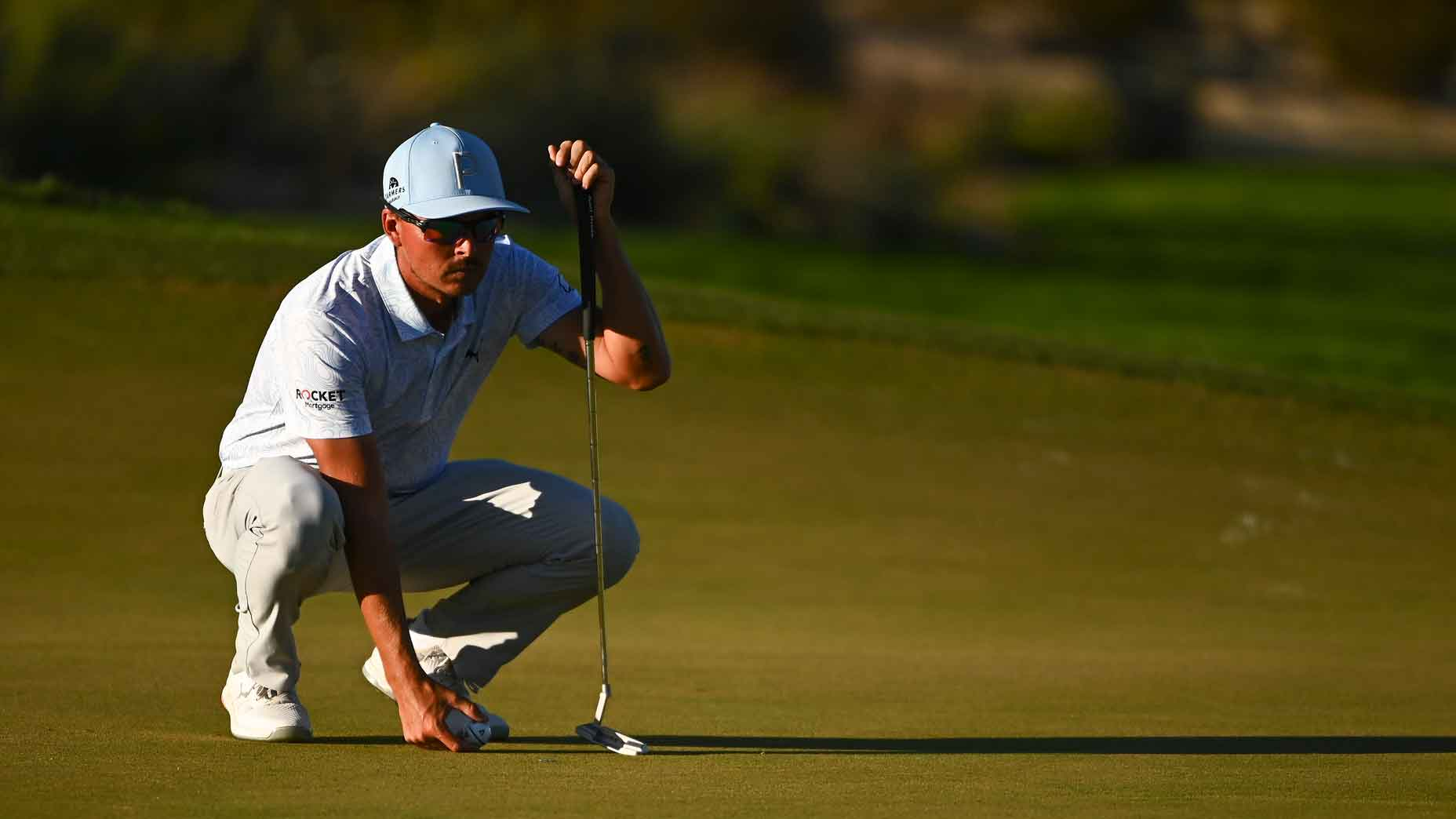 Rickie Fowler crouches over a putt