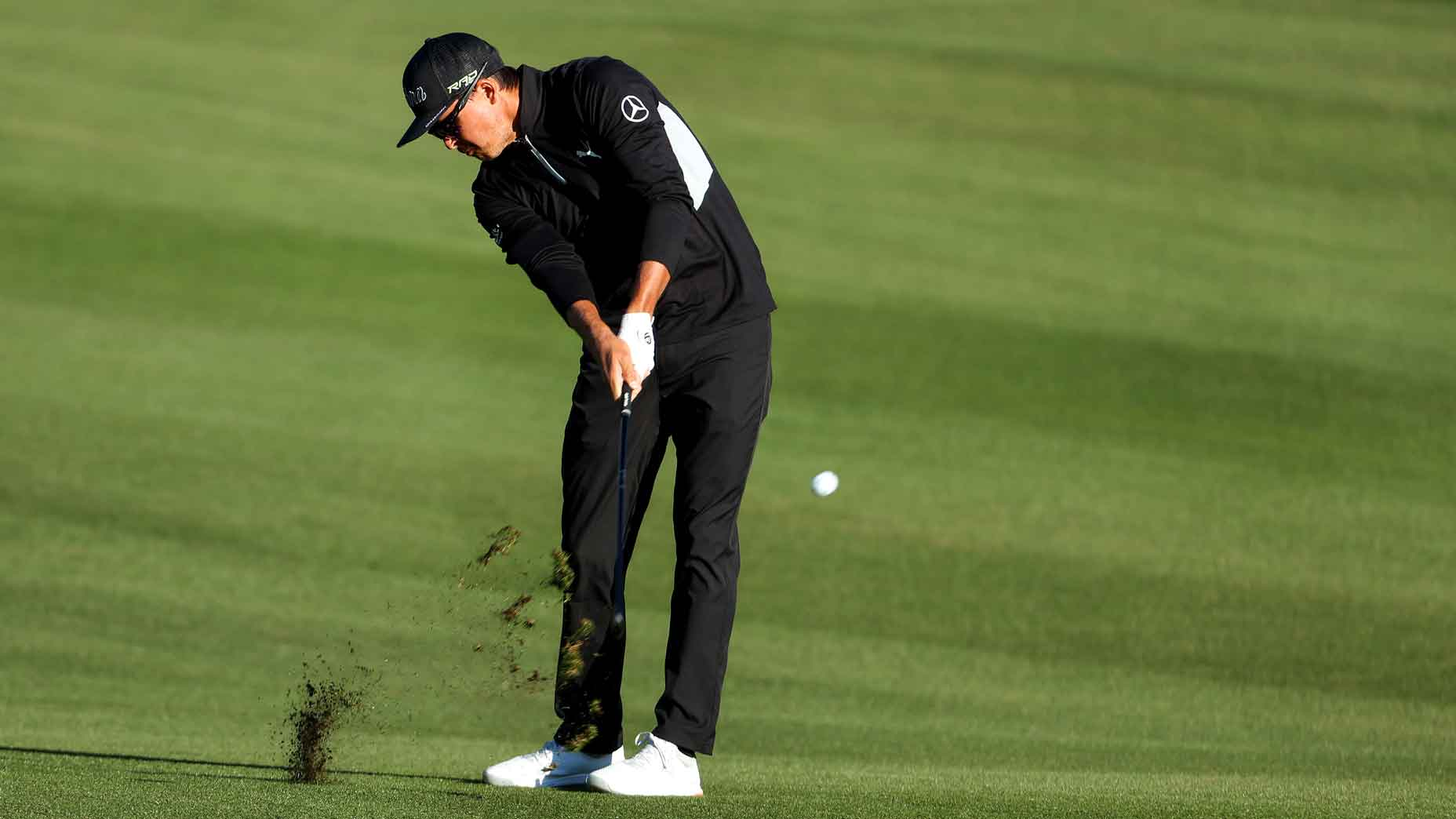 A photo of Rickie Fowler at impact position