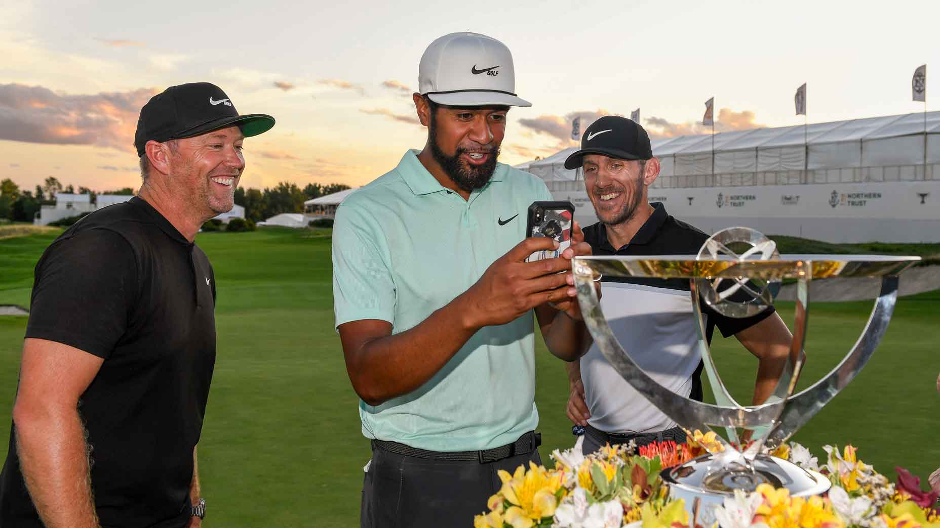 Tony Finau FaceTimes with his family next to the Northern Trust trophy
