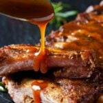 a spoon of barbecue sauce dripping on a platter of spare ribs