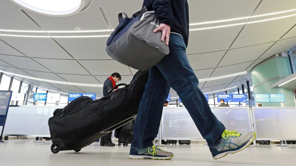 man traveling with golf clubs