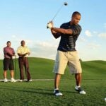 Four golfers on tee box of golf course