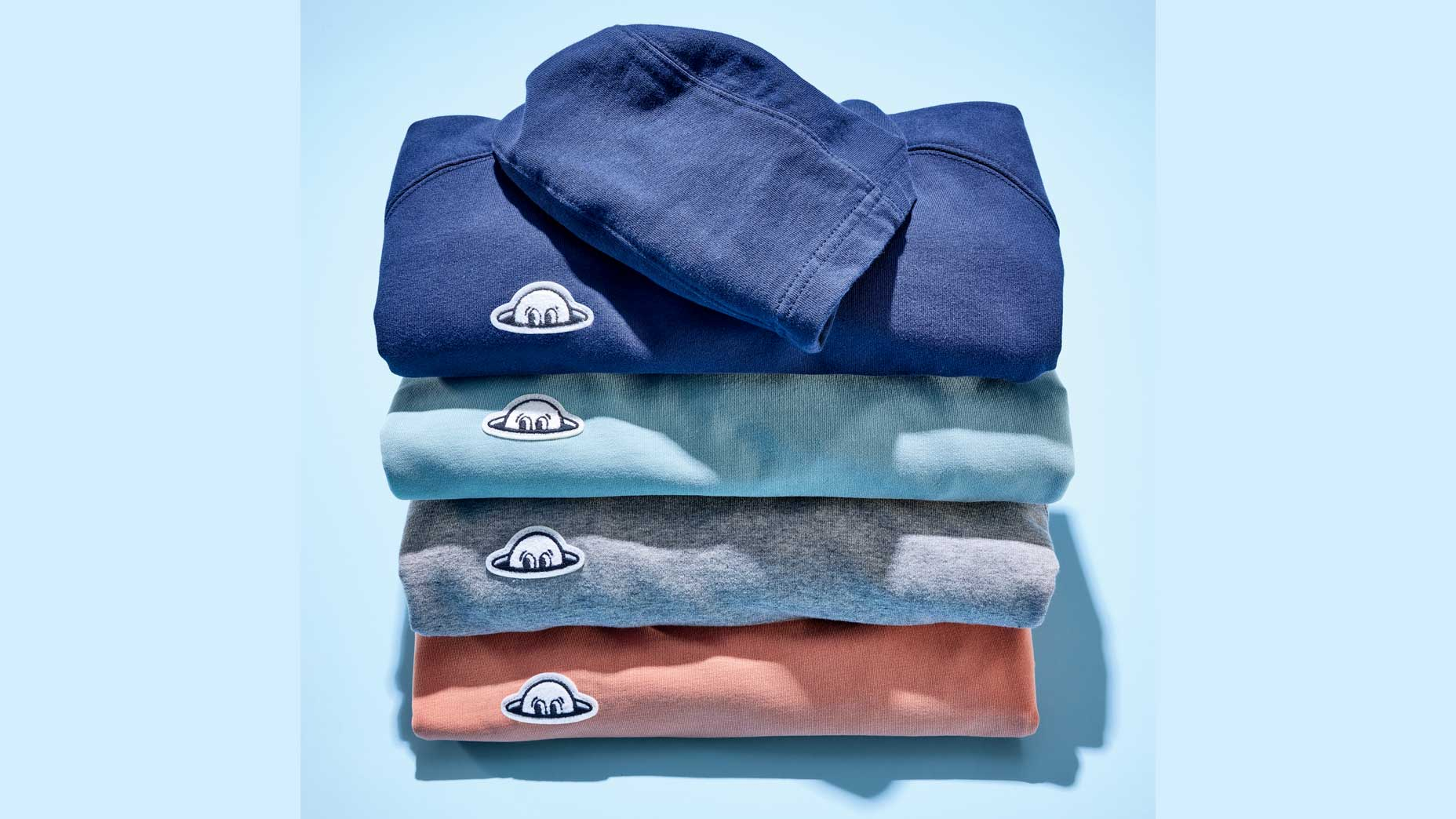 A stack of four Radmor Higgins golf hoodies against a baby blue background