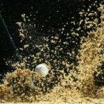 Sand flies up as a golf ball in a bunker is struck by a wedge in front of a black background