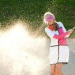 a woman hits a big splash of sand in a bunker