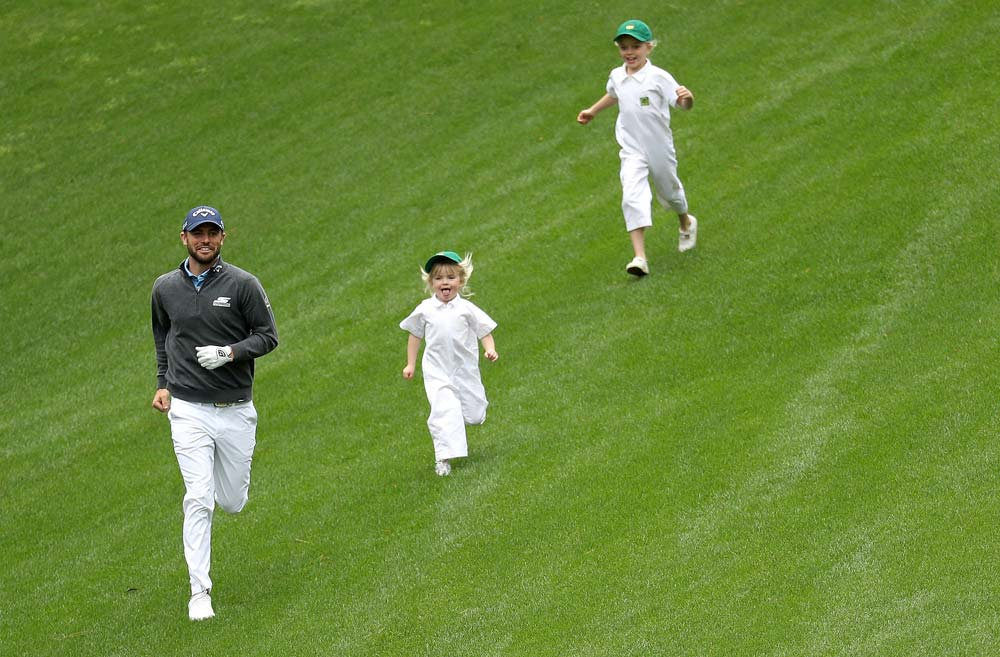 <p/>Wesley Bryan runs down a hill during the Masters Par 3 Contest with two young caddies in tow.